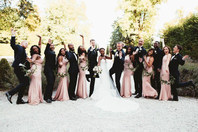 Wedding party portrait with Pronovias wedding dress, pink bridesmaid dresses and tuxedos