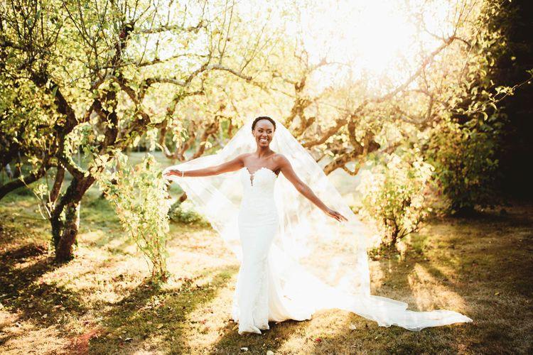 Black bride in strapless Pronovias wedding dress and veil for destination wedding with pink bridesmaid dresses
