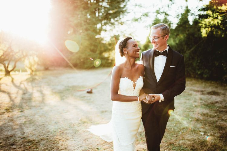 Bride and groom laughing at holding hands during golden hour