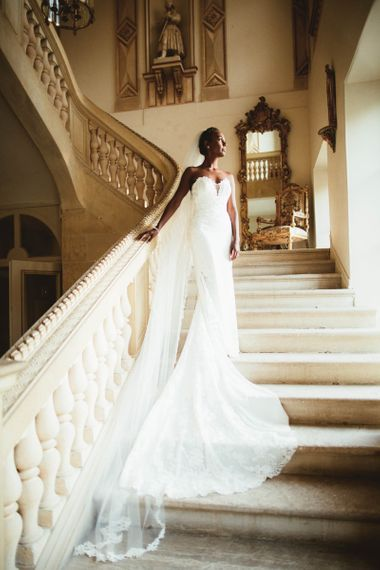Bride in strapless Pronovias wedding dress standing on the stairs at Chateau La Durantie, France