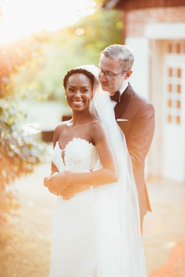 Groom in tuxedo embracing his bride in a strapless wedding dress