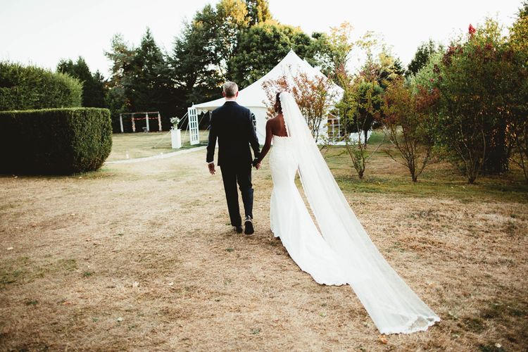 Bride and groom walking towards their marquee reception at Chateau La Durantie, France