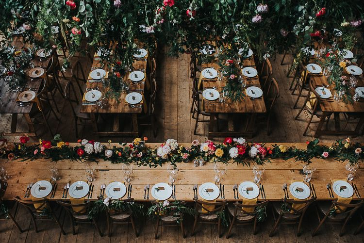 Long Wooden Banquet Tables | Yellow Napkins | Pink, Orange and Yellow Table Flowers with Foliage | Kraft Label Place Settings | Wedding Reception at Abbey Hall Creative Space | 'Frida Kahlo' Flower Crown, Halfpenny London Bridal Separates and Colourful Bouquets with Peonies for Suffolk Wedding | From The Smiths Photography