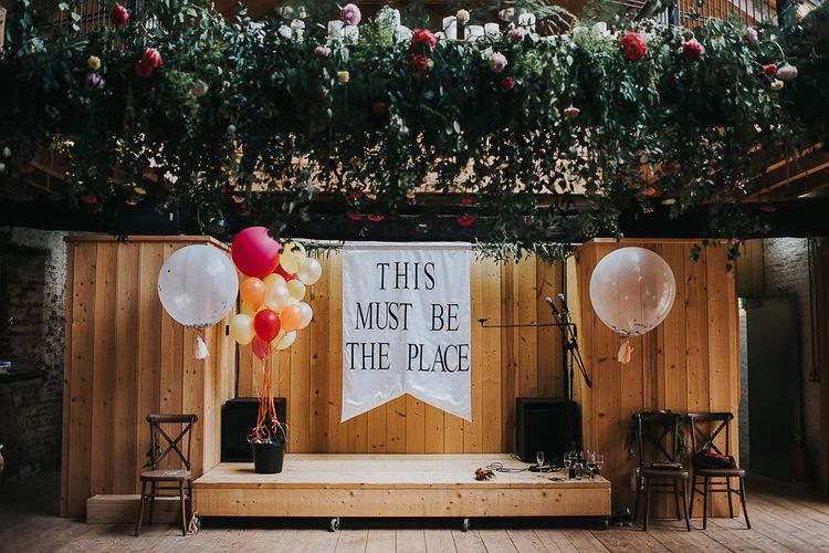 This Must Be The Place Flag | Hanging Floral Installation | Confetti Balloons | Red, Orange and Yellow Balloons | Wedding Reception at Abbey Hall Creative Space | 'Frida Kahlo' Flower Crown, Halfpenny London Bridal Separates and Colourful Bouquets with Peonies for Suffolk Wedding | From The Smiths Photography