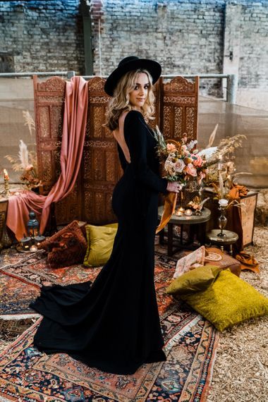 Alternative Bride in Black Wedding Dress and Fedora Bridal Hat Standing at the  Altar Full of Moroccan Rugs, Screens and Cushions