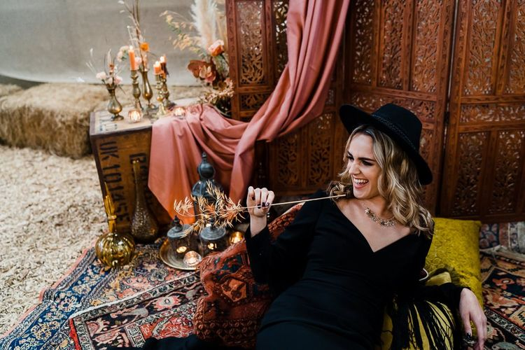 Alternative Bride in Black Wedding Dress and Fedora Bridal Hat  Lounging on the Moroccan Rugs and Cushions