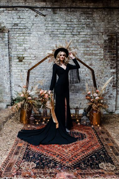 Bride in Black Wedding Dress and Fedora Hat Standing in Front of a Wooden Frame Altar with Dried Flower Arrangements and Moroccan Rug