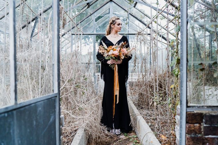 Bride in a Black Wedding Dress Standing in a Glasshouse
