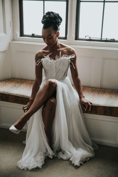 Black bride in Mira Zwillinger wedding dress with feathers