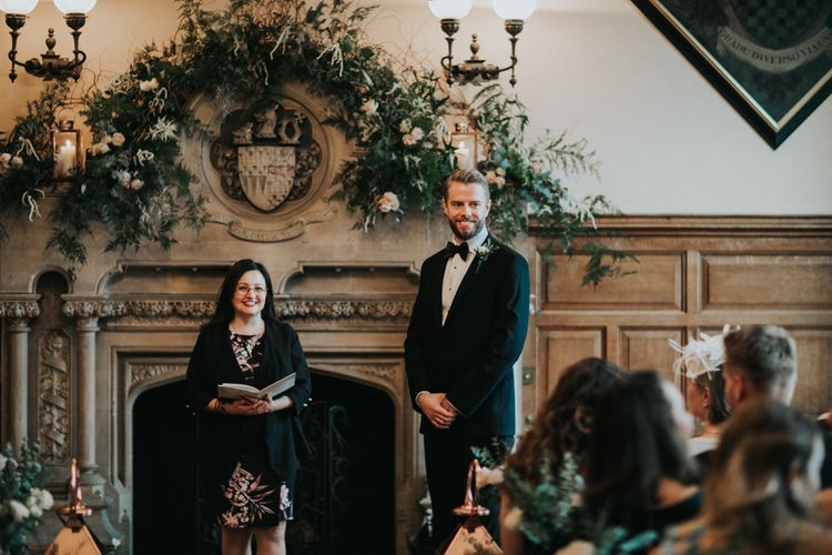 Groom in tuxedo standing at the altar of The Elvetham wedding venue