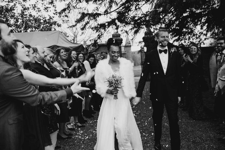 Confetti moment with bride in faux fur coverup