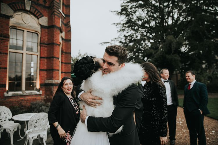 Bride in white faux fur coverup hugging a wedding guest