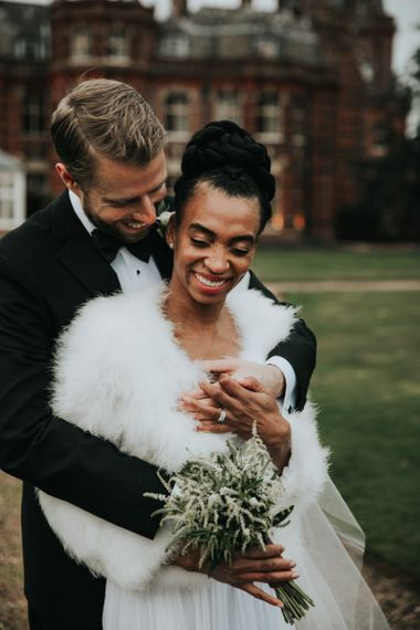 Groom in tuxedo embracing his bride in feather coverup