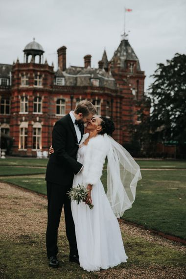 Bride and groom kissing with  The Elvetham wedding venue in the backdrop