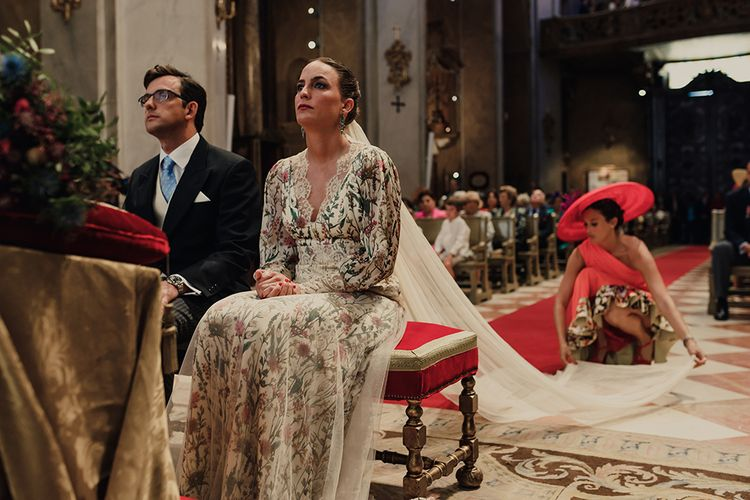 Spanish Church Wedding Ceremony with Bride in Floral Print Bespoke Wedding Dress by From Lista With Love and Long Wedding Veil and Groom in Traditional Morning Suit