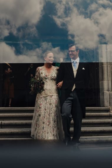 Bride in Floral Print Bespoke Wedding Dress by From Lista With Love and Groom in Traditional Morning Suit Exiting The Church