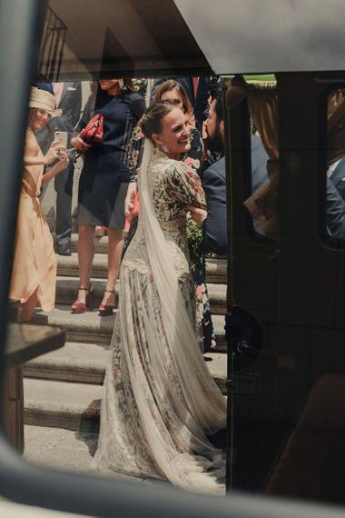 Bride in Floral Print Bespoke Wedding Dress by From Lista With Love and Groom in Traditional Morning Suit Being congratulated by Wedding Guests