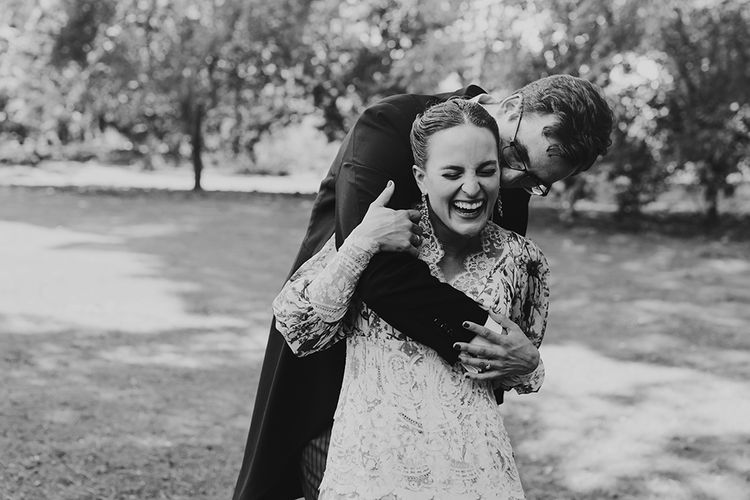 Bride in Floral Print Bespoke Wedding Dress by From Lista With Love and Groom in Traditional Morning Suit  Laughing