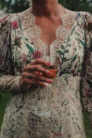Bride in Floral Wedding Dress Holding Flute of Pink Champagne with Red Nail Polish