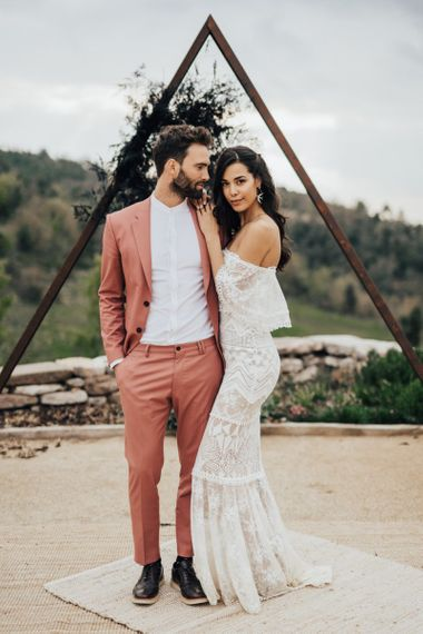 Boho Bride in Bardot Grace Loves Lace Wedding Dress and Groom in Coral Suit Standing in Front of a Wooden Triangle Altar