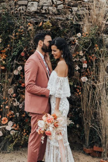 Bride in Off The Shoulder Lace Wedding Dress and Groom in Dusky Pink Suit Laughing by a Dried Flower Arrangement
