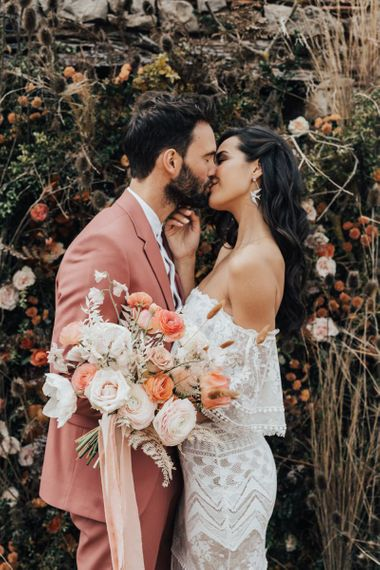 Bride in Off The Shoulder Lace Wedding Dress and Groom in Dusky Pink Suit  Kissing, Holding a White and Peach Wedding Bouquet