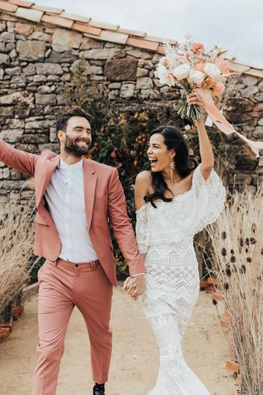 Stylish Bride in Grace Loves Lace Wedding Dress and Groom in Dusky Pink Suit Celebrating