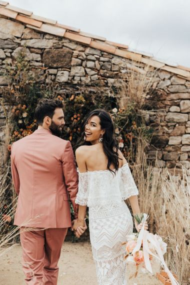 Stylish Bride in Grace Loves Lace Wedding Dress and Groom in Dusky Pink Suit Holding Hands Laughing