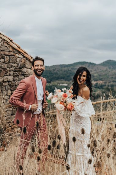 Stylish Bride in Grace Loves Lace Wedding Dress and Groom in Dusky Pink Suit Laughing in the Reeds
