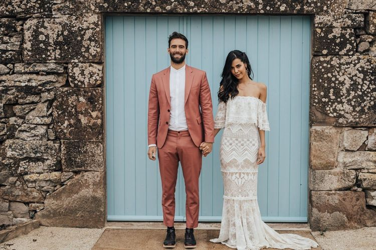 Bride in Bardot Grace Love Laces Wedding Dress and Groom in Coral Wedding Suit Holding Hands