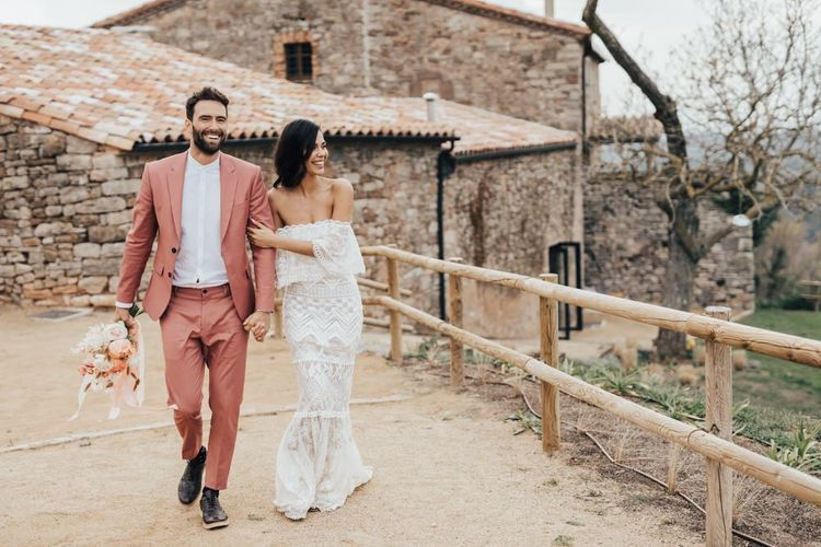 Bride in Bardot Grace Loves Lace Wedding Dress and Groom in Coral Suit Walking Arm in Arm at Barcelona Venue This Must Be the Place