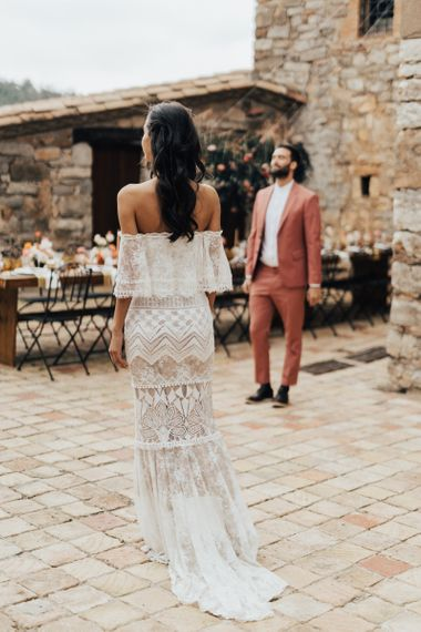 Bride in Bardot Grace Loves Lace Wedding Dress approaching Her Groom for a First Look in a Coral Suit