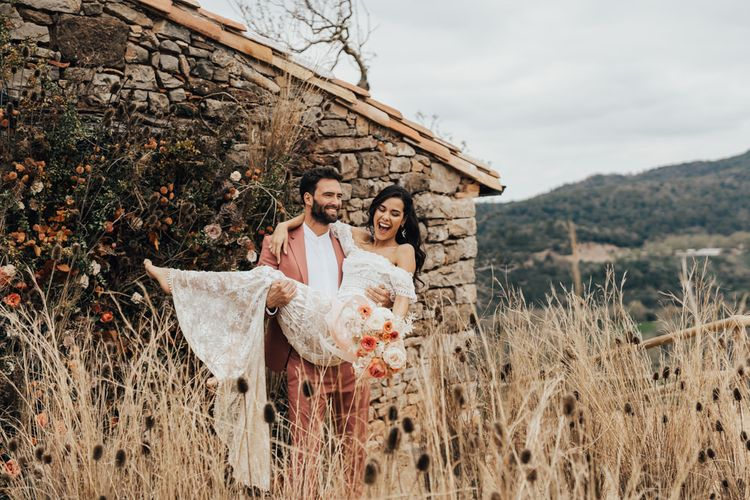 Groom in Coral Wedding Suit Picking Up His Bride in a Grace Loves Lace Wedding Dress