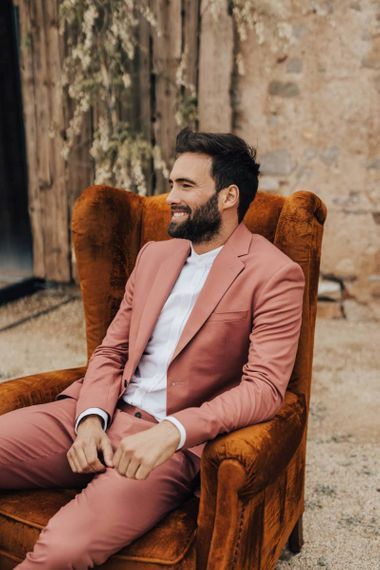 Groom in Coral Suit Sitting on an Armchair