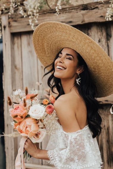 Beautiful Bride in Straw Hat Holding a White and Coral Wedding Bouquet