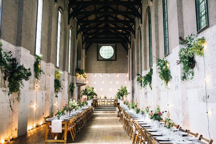 Lofty, long table reception with hanging foliage at Dilston Grove Barn Wedding Venue