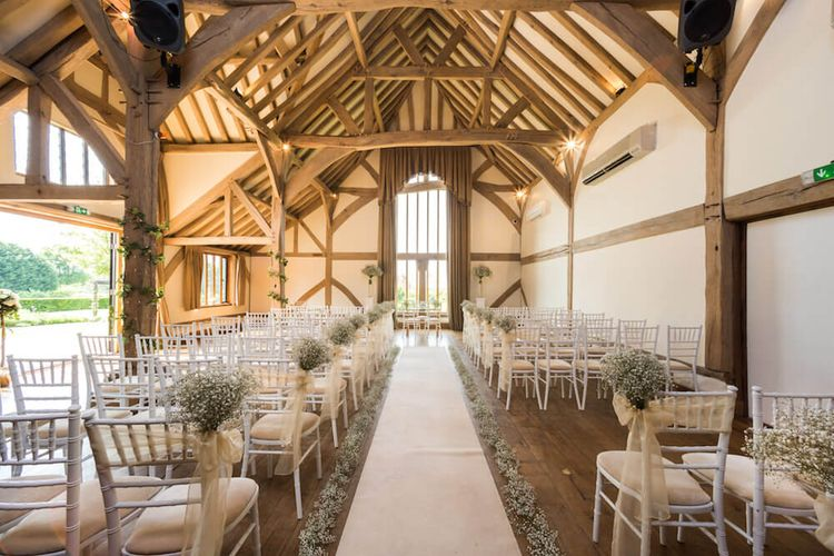 Barn Wedding Venues Cain Manor with high exposed beams for ceremony with white aisle runner