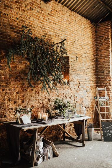 Gift and guest book table under hanging branch against exposed brick wall of the barn.