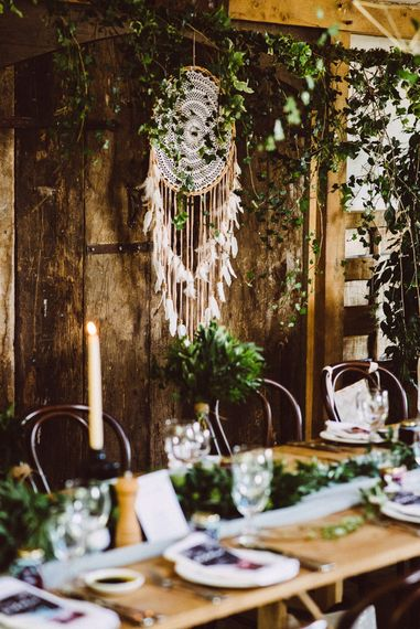 Hanging giant, white, dreamcatcher and greenery behind the bride at long table reception, Cripps Barn