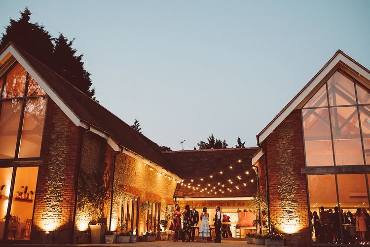 Outdoor shot of Millbridge Court Barn Wedding Venue at twilight with hanging festoons