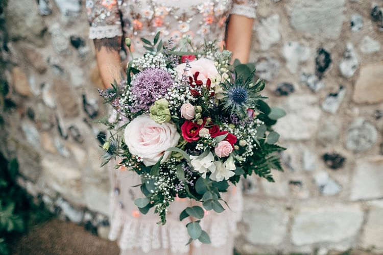 Wedding Bouquet With Thistles And Roses // Beautiful DIY Village Hall Wedding For Under £5k // Guests Made Food // Bride Wears Needle & Thread // Images By Dale Weeks Photography