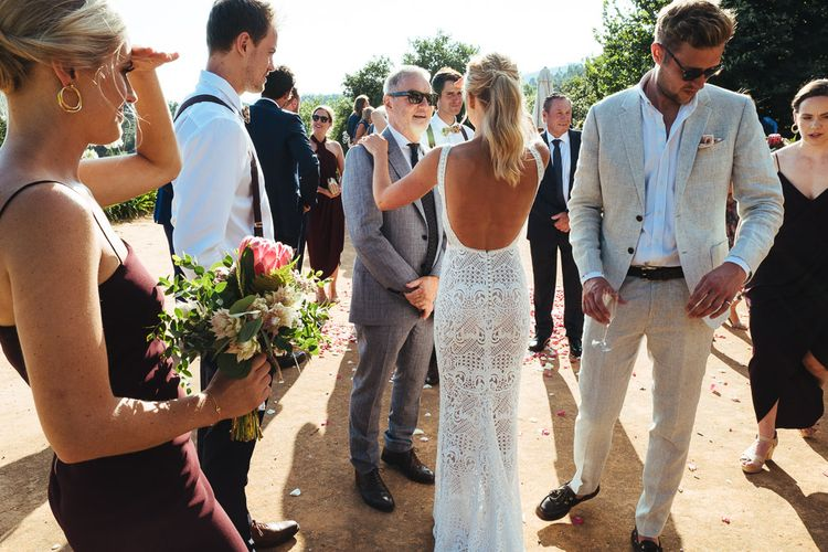 Bride in Backless Pallas Couture Esila Wedding Dress Greeting Wedding Guests