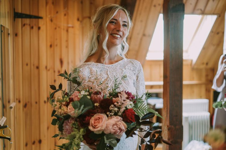 Bride in Grace Loves Lace Inca Gown with Boat Neck, Lace Sleeves and Low Back | Bridal Bouquet of Burgundy and Blush Flowers with Foliage | Mykonos Rewritten Bridesmaid Dresses for an Epic Clifftop Coastal Wedding | Nic Ford Photography
