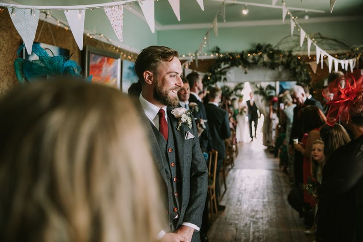 Groom in Three-Piece Grey Herringbone Suit with Burgundy Tie and Buttons | Blush Buttonhole | Foliage Arch | Pastel Bunting | Fairy Lights | Wedding Ceremony at The Druidstone | Mykonos Rewritten Bridesmaid Dresses for an Epic Clifftop Coastal Wedding | Nic Ford Photography