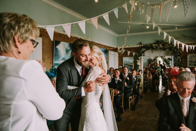 Bride in Grace Loves Lace Inca Gown with Boat Neck, Lace Sleeves and Low Back | Personalised Embroidered Veil by Daisy Sheldon | Groom in Three-Piece Grey Herringbone Suit with Burgundy Tie and Buttons | Foliage Arch | Pastel Bunting | Fairy Lights | Wedding Ceremony at The Druidstone | Mykonos Rewritten Bridesmaid Dresses for an Epic Clifftop Coastal Wedding | Nic Ford Photography