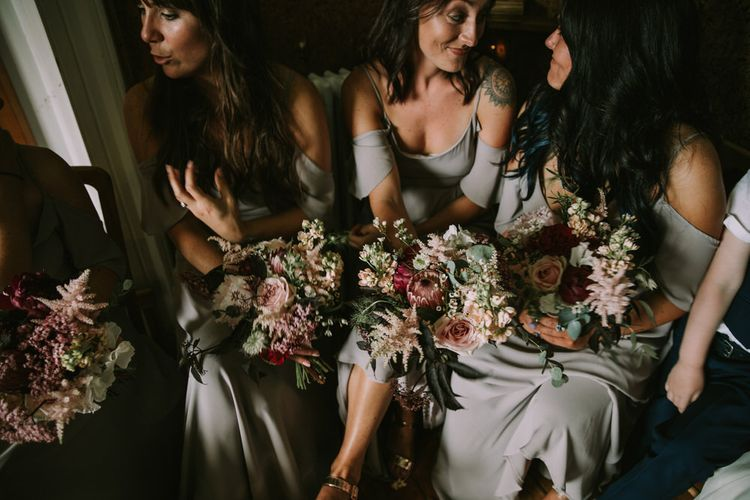 Bridesmaids in Grey Cold Shoulder Dresses by Rewritten | Bouquets of Blush and Pink Flowers with Foliage | Wedding Ceremony at The Druidstone | Mykonos Rewritten Bridesmaid Dresses for an Epic Clifftop Coastal Wedding | Nic Ford Photography