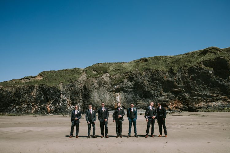 Groom in Three-Piece Grey Herringbone Suit with Burgundy Tie and Buttons | Groomsmen in Mismatched Navy Suits with Blush Pink Ties | Mykonos Rewritten Bridesmaid Dresses for an Epic Clifftop Coastal Wedding | Nic Ford Photography