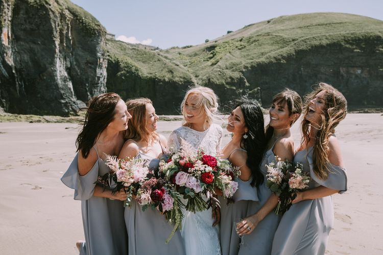 Bride in Grace Loves Lace Inca Gown with Boat Neck, Lace Sleeves and Low Back | Bridesmaids in Grey Cold Shoulder Dresses by Rewritten | Bridal Party Bouquets of Burgundy and Blush Flowers with Foliage | Mykonos Rewritten Bridesmaid Dresses for an Epic Clifftop Coastal Wedding | Nic Ford Photography