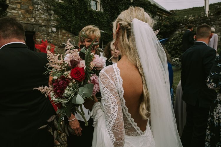 Bride in Grace Loves Lace Inca Gown with Boat Neck, Lace Sleeves and Low Back | Personalised Embroidered Veil by Daisy Sheldon | Aurora Hair Comb by Tilly Thomas Lux  | Bridal Bouquet of Burgundy and Blush Flowers with Foliage | Mykonos Rewritten Bridesmaid Dresses for an Epic Clifftop Coastal Wedding | Nic Ford Photography