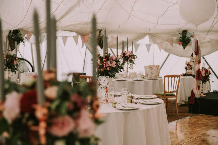 Marquee with Draped Ceiling at The Druidstone | Pastel Bunting | Grey Tapered Candles | Rose Gold Candelabras | Giant White Balloons with Grey, Blush and Burgundy Tassels | Table Centrepieces of Blush and Burgundy Flowers with Foliage | Mykonos Rewritten Bridesmaid Dresses for an Epic Clifftop Coastal Wedding | Nic Ford Photography